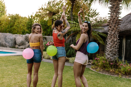 Group of friends playing balloon pop game