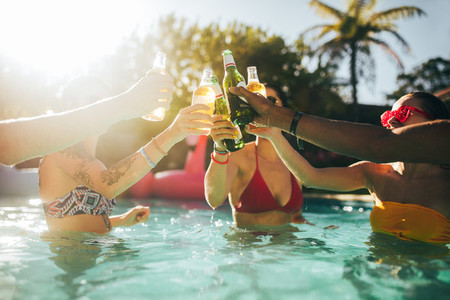 Friends having beers in swimming pool party