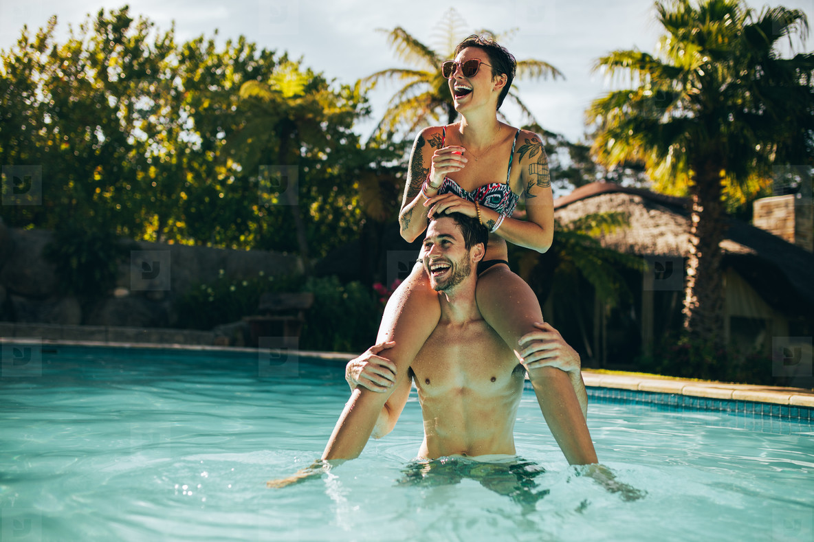 Young couple having fun in swimming pool