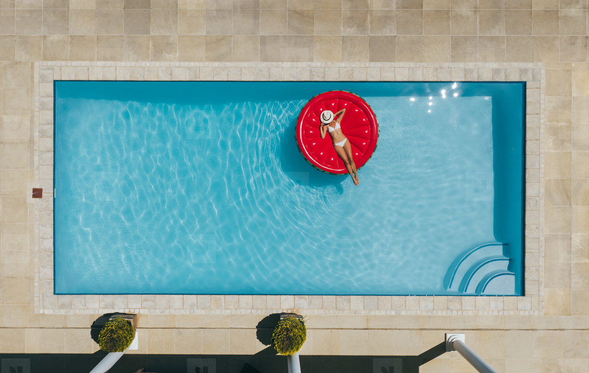 Woman sunbathing on inflatable mattress in pool
