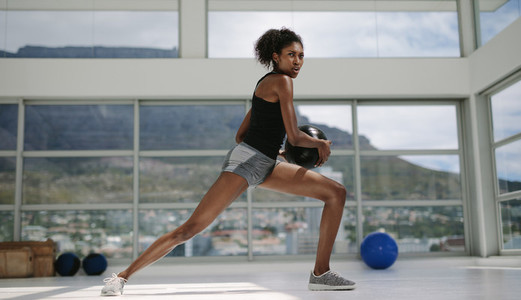 African girl doing stretching exercise with medicine ball