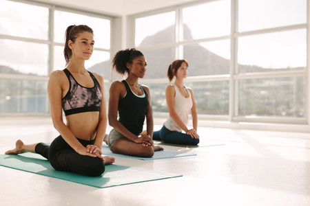 Healthy women doing yoga in gym class