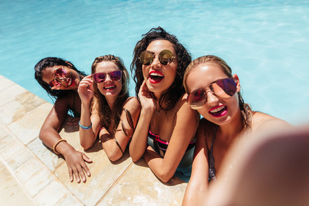 Group of friends taking selfie photo in pool