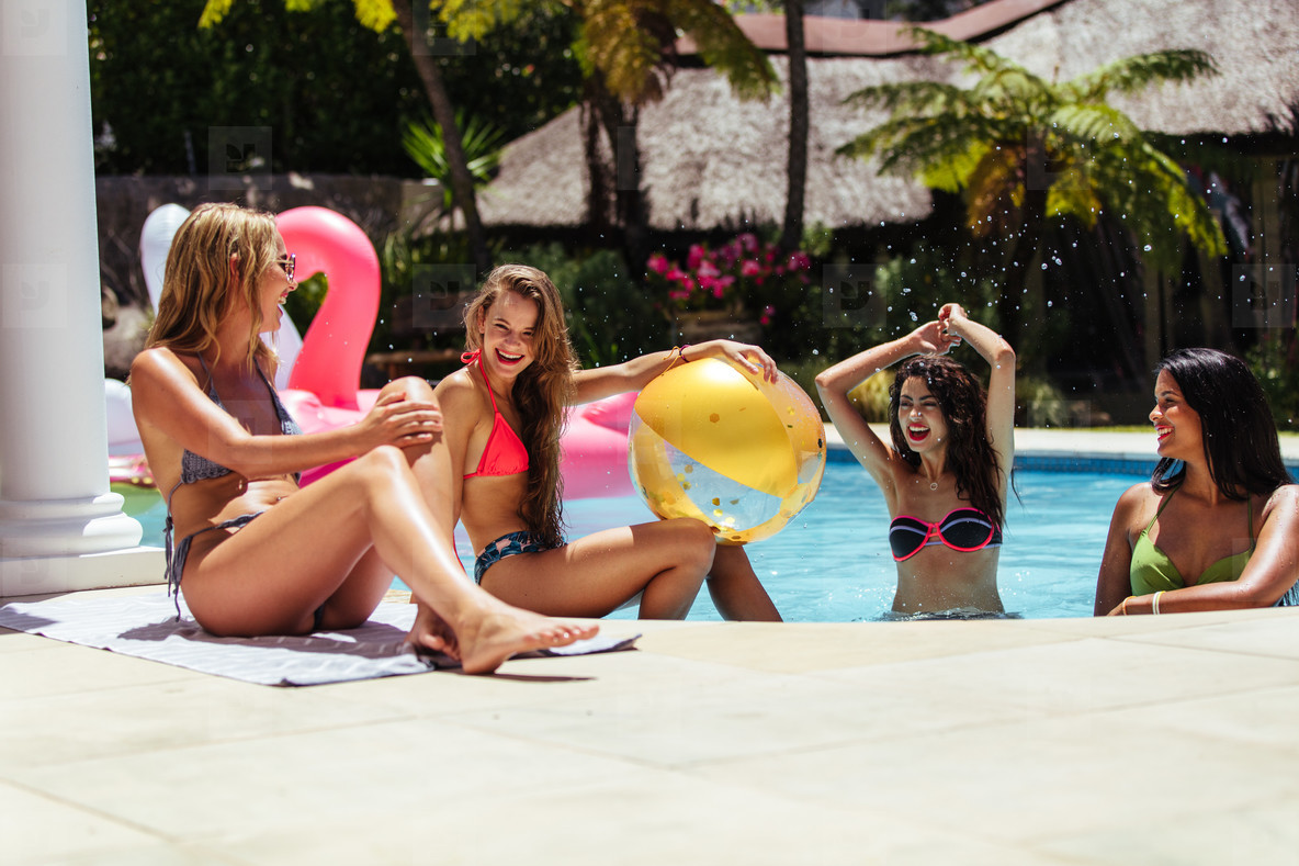 Group of female friends having fun in swimming pool