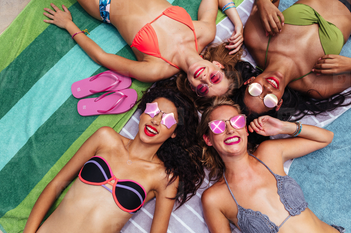 Group of happy women hanging out at poolside