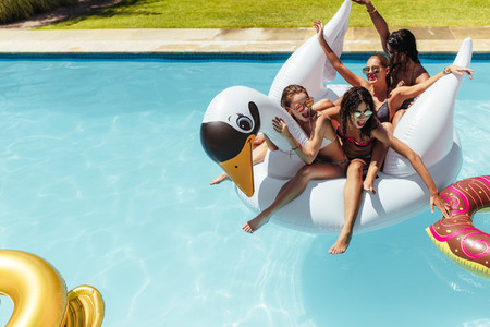 Friends enjoying themselves on a inflatable swan in pool