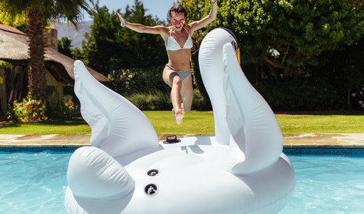 Woman jumping on to an inflatable toy in pool