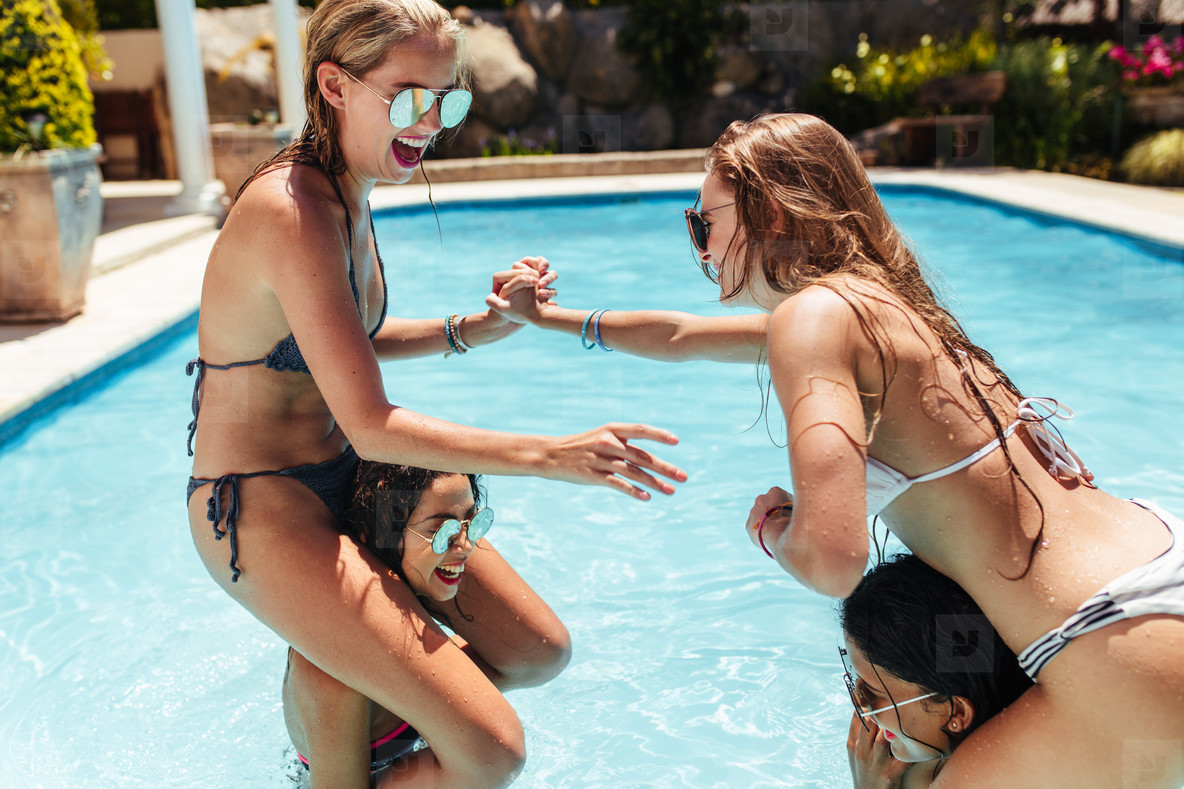 Women in bikinis having fun in swimming pool