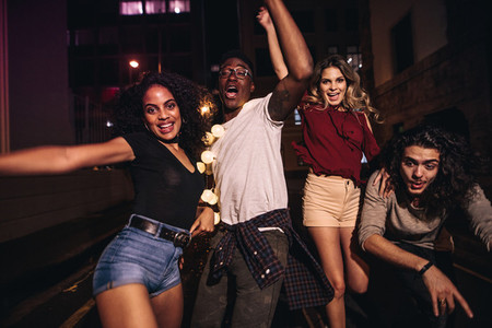 Friends having outdoor party in the city street at night