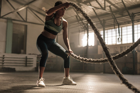 Athlete working out with battle ropes at cross gym