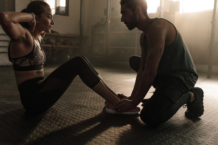 Male coach assisting woman in doing sit ups at gym