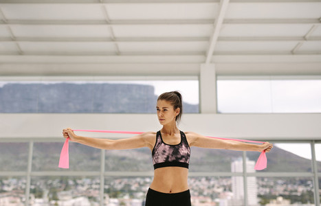 Healthy woman exercises with resistance ban