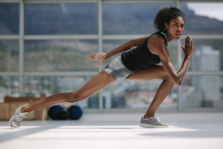 Slim african woman exercising in gym