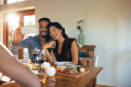 Couple taking selfie at dinner party with friends