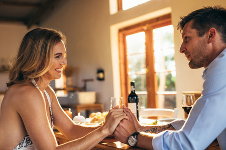 Loving young couple holding hands at dining table