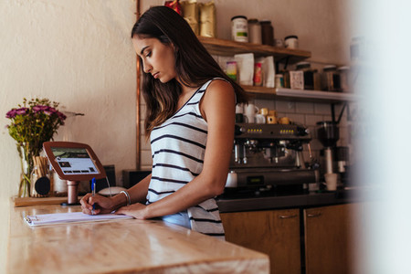 Woman entrepreneur standing at the billing counter of her cafe