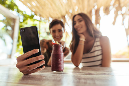 Friends taking selfie with a smoothie on the table