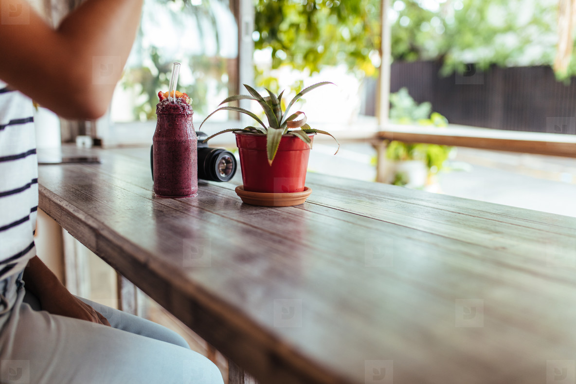 Smoothie jar on a table beside a flower pot