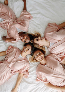 Bride with bridesmaids lying on bed and smiling