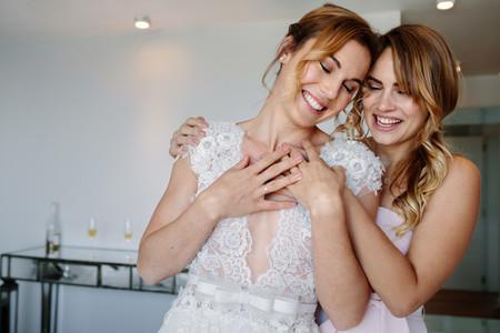 Bridesmaid giving a tender hug to beautiful bride