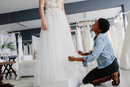 Smiling woman making adjustment to bridal gown