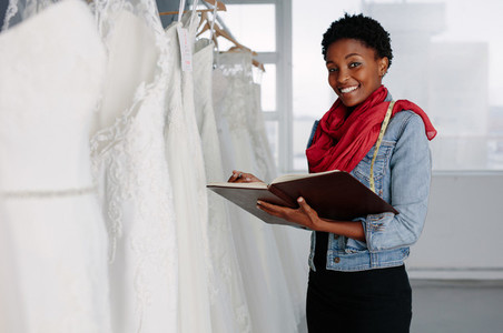 Female bridal wear designer working in boutique