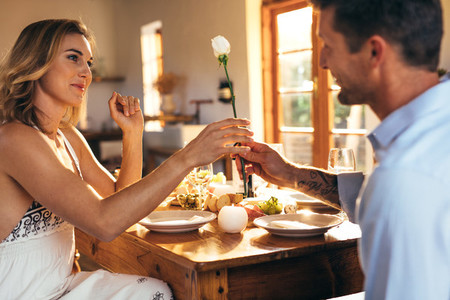 Romantic couple sitting at dining table at home