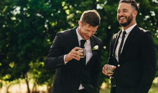 Groom and best man drinking at wedding party