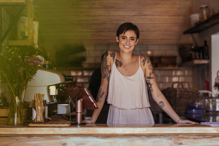 Woman entrepreneur standing at the counter of her cafe