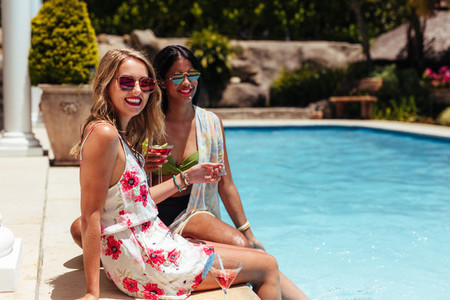 Happy women with drinks relaxing at the poolside
