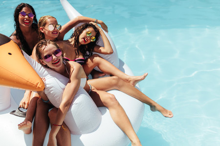 Beautiful women floating on inflatable swan in pool