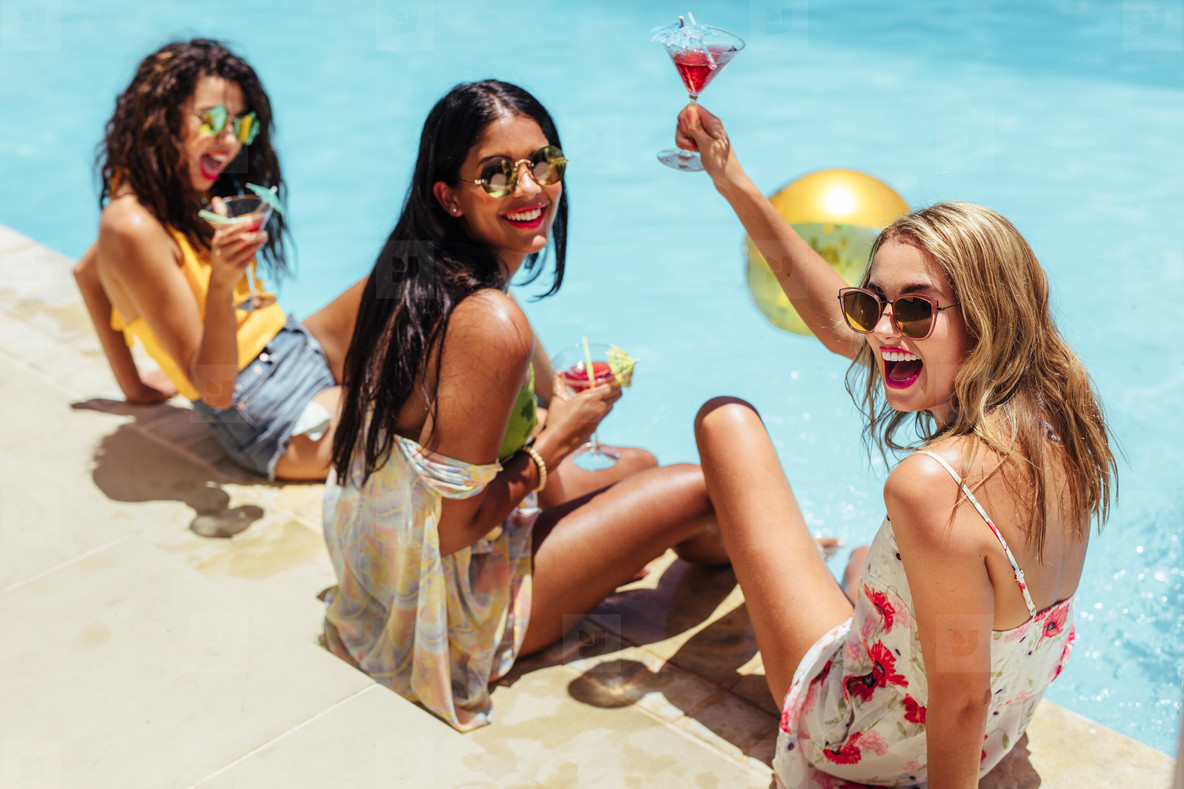 Girls hanging out by the pool with drinks