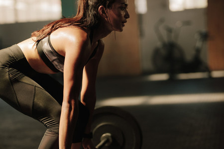 Fitness model performing weight lifting exercises