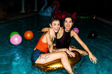 Female friends enjoying evening pool party