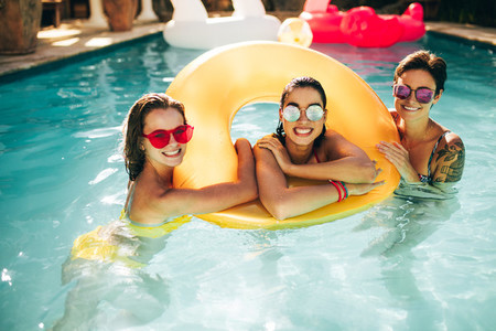 Cheerful women in pool with inflatable ring
