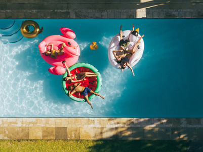 Friends chilling on air mattresses in swimming pool