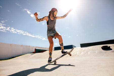 Female skater skateboarding at skate park
