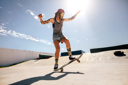 Female skater skateboarding at skate park