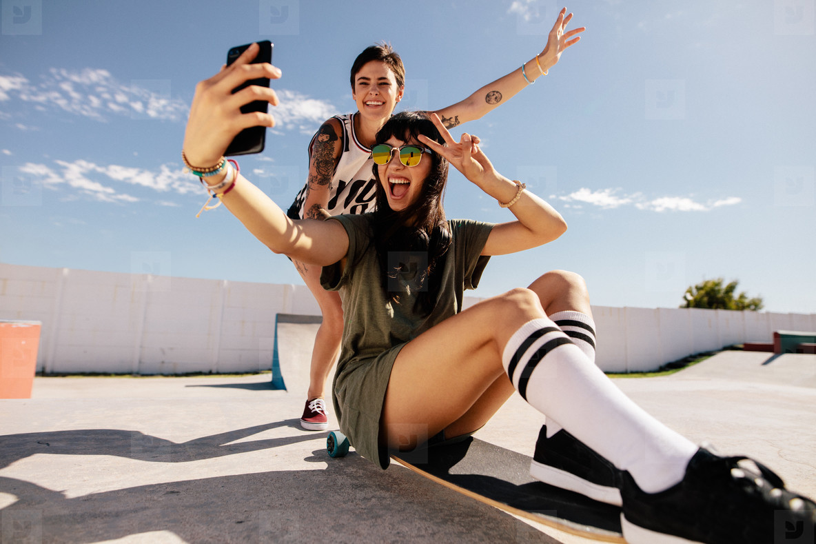 Girls skateboarding and taking selfie