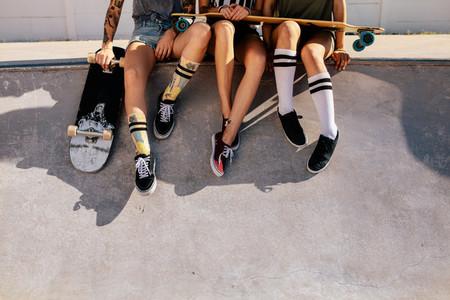 Legs of women sitting on ramp at skate park