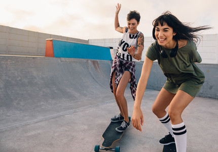 Girls riding on skateboards and having fun at skate park
