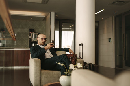 Business traveler waiting in airport lounge using phone
