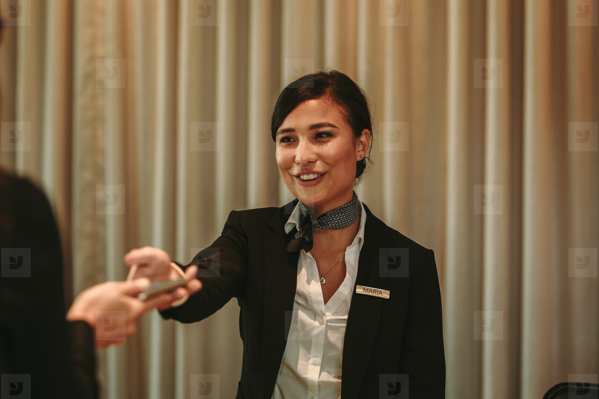 Receptionist receiving payment for hotel room from client