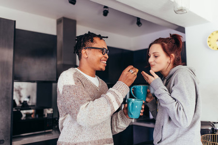 Interracial couple having coffee together in morning