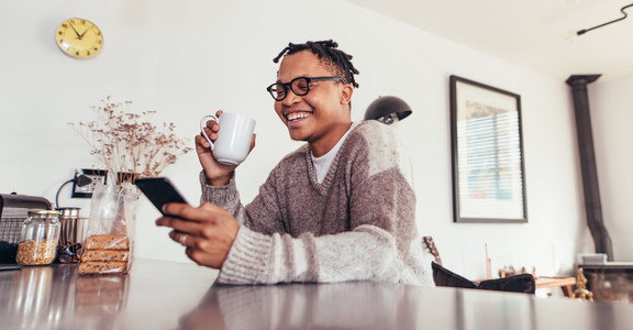 African man using phone and drinking coffee