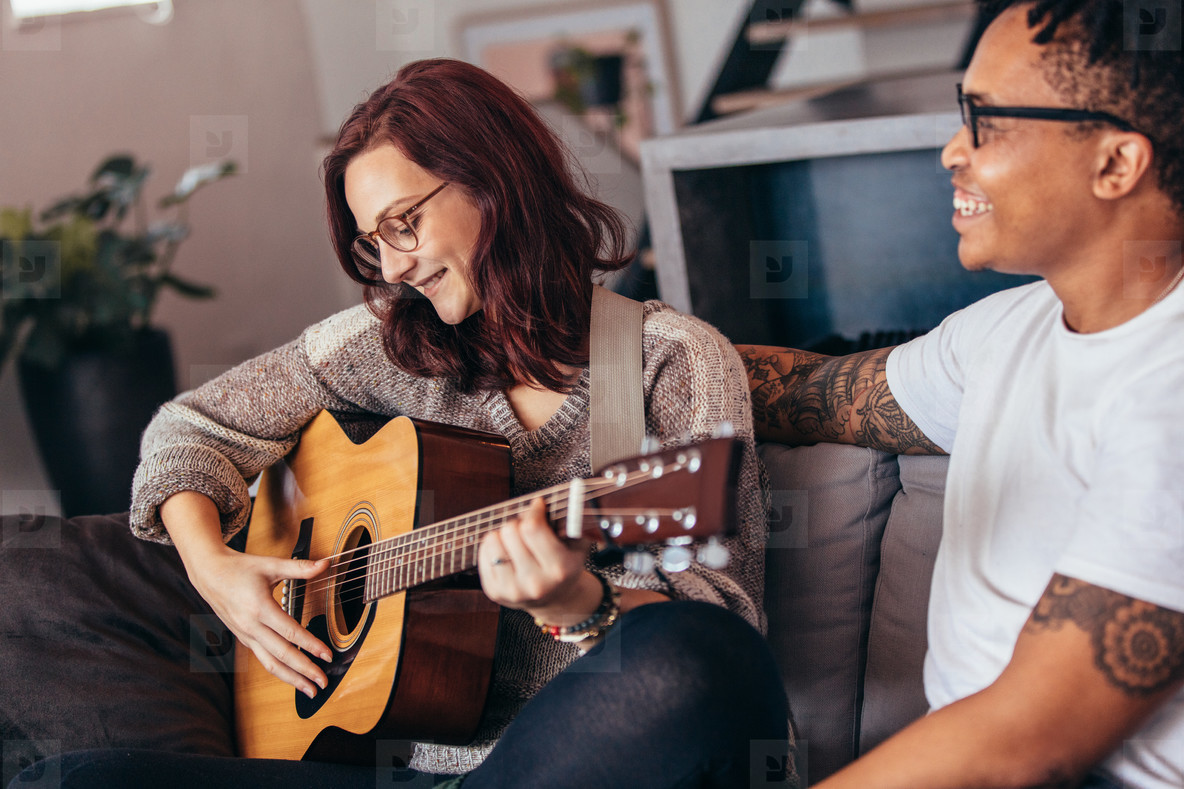 Woman playing guitar with her boyfriend at home
