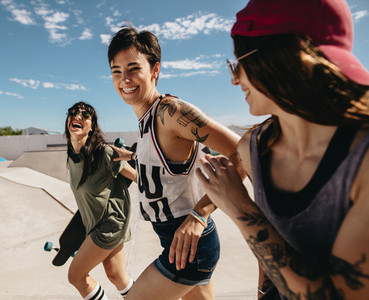 Women friends running outdoors at skate park