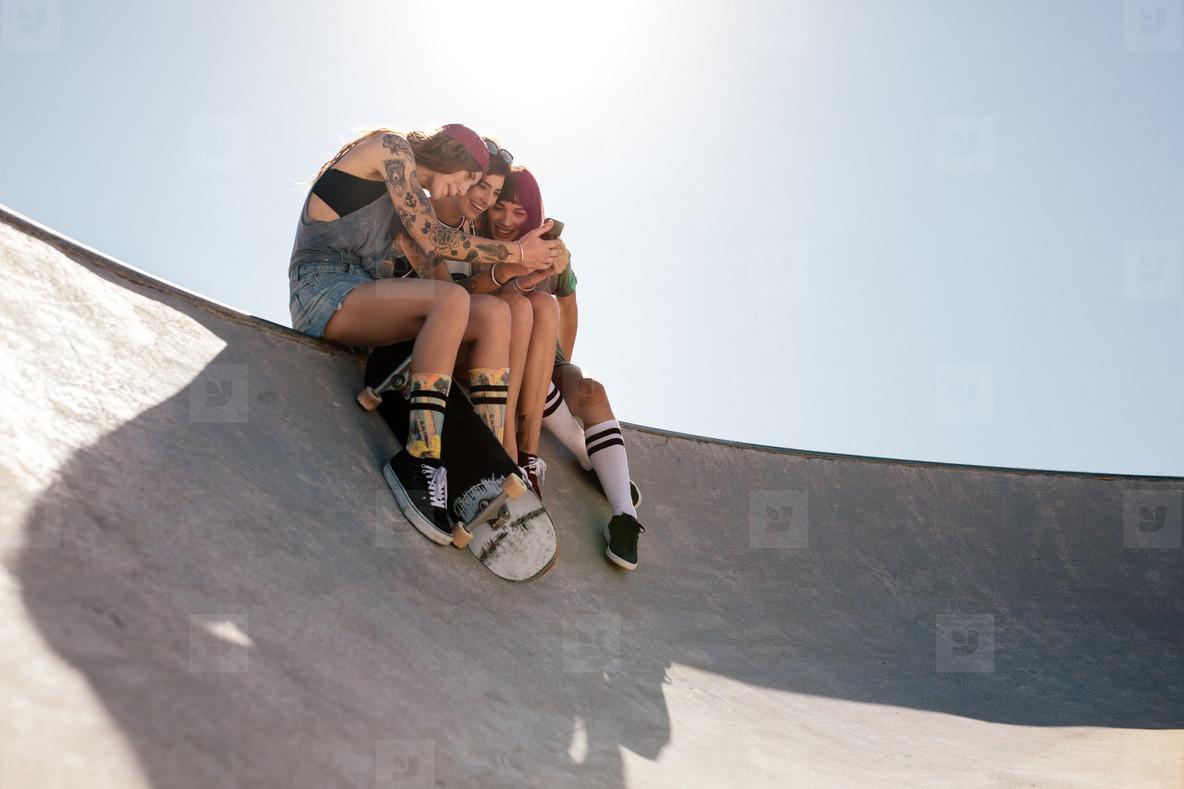 Women skaters using mobile phone at skate park