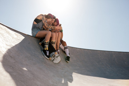 Women skaters using mobile phone at skate park