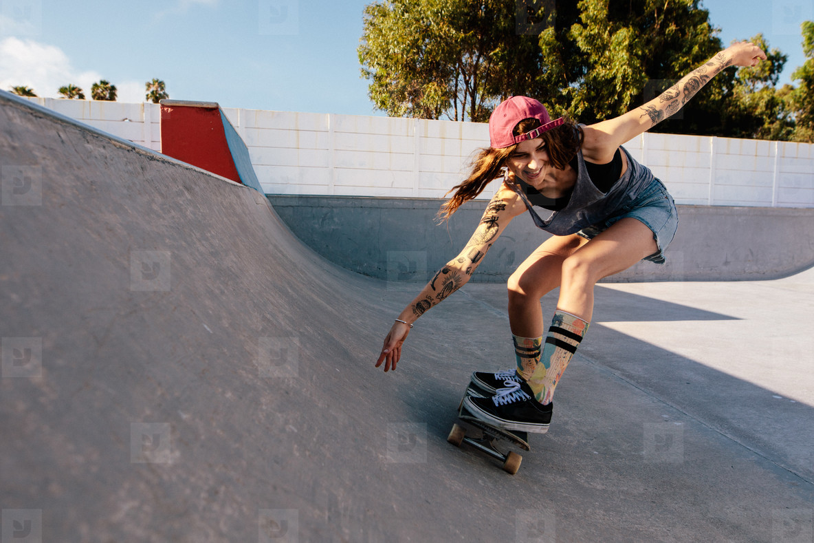 Woman practising skateboarding at skate park